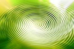 抽象绿色发光的打旋的水作用背景 免版税库存图片
