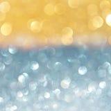 抽象bokeh点燃与金子,并且蓝色闪烁 图库摄影