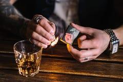 抽雪茄的一个年轻人在客栈 免版税库存图片