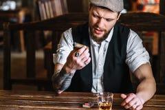 抽雪茄的一个年轻有胡子的人在客栈 库存照片