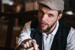 抽雪茄的一个年轻有胡子的人在客栈 免版税库存图片