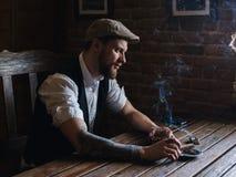 抽雪茄的一个年轻有胡子的人在客栈 库存图片