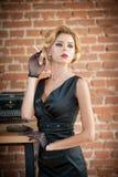 抽香烟的黑礼服的年轻美丽的短发白肤金发的妇女 有电影明星神色的典雅的浪漫神奇夫人 库存图片