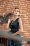 抽香烟的黑礼服的年轻美丽的短发白肤金发的妇女 有电影明星神色的典雅的浪漫神奇夫人 免版税库存图片