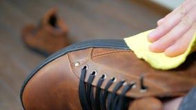拂去有一块黄色旧布的手棕色皮鞋的灰尘 股票视频