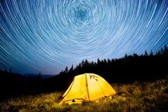担任主角在夜山森林和一个发光的野营的帐篷上的圈子 免版税库存照片