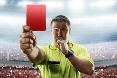 担任仲裁显示红牌在足球场 免版税库存图片