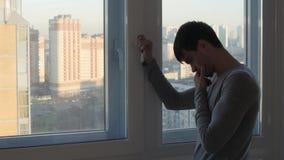 担心的人立场和哭泣在窗口附近 股票录像