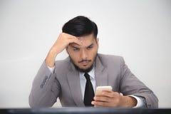 担心的商人与智能手机一起使用 免版税库存图片