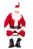 担心的圣诞老人坐椅子 免版税库存图片