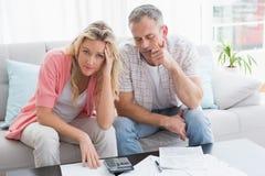 担心的在长沙发的夫妇计算的票据 免版税库存照片