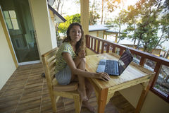 担心的女孩是有一台膝上型计算机的一位自由职业者在公寓房大阳台在海附近 免版税库存照片