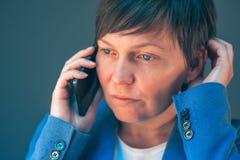 担心的女实业家在令人不快的电话谈话时 库存照片
