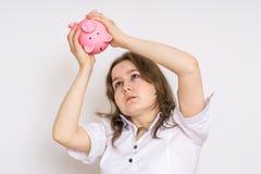 年轻担心的妇女在空的贪心金钱银行看 库存照片