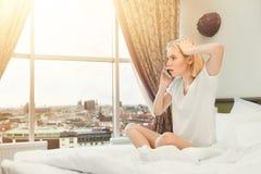 担心的妇女谈话在电话在旅馆客房 免版税图库摄影