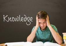 担心的学生男孩在反对灰色黑板的桌上有知识文本的 免版税图库摄影