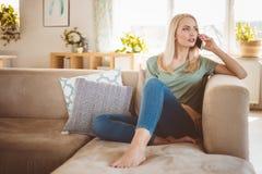 担心的年轻女人在家谈话在沙发的机动性 库存照片