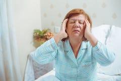 担心的老妇人在家有头疼 免版税库存照片