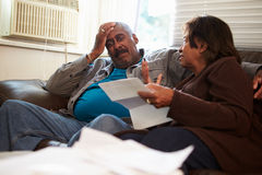 担心的资深夫妇坐看票据的沙发 免版税图库摄影