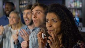 担心的队支持者看着电视竞争,小组在体育比赛的爱好者 股票录像