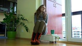 担心的结冰的妇女坐幅射器 等待的温暖的季节开始 股票录像