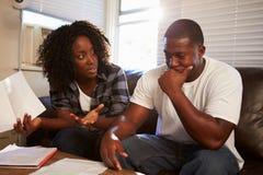 担心的年轻夫妇坐看票据的沙发 库存照片