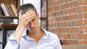 担心的Manwith头疼,创造性的顶楼办公室 免版税库存照片