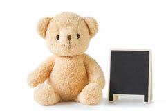 负担玩偶与黑板坐被隔绝的白色背景 免版税库存照片