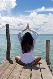 担任在海的妇女瑜伽职务 免版税库存照片