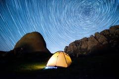 担任主角在山和一个发光的野营的帐篷上的圈子 库存照片