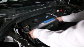 拆卸一辆电混合动力车辆的引擎盖子的技工 股票视频