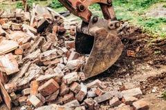 拆毁大厦和汇聚残骸的反向铲挖掘机在房子建筑时 免版税库存照片