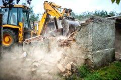 拆毁小大厦的水泥砖墙推土机 库存照片
