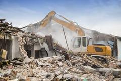 拆毁营房的挖掘机 库存照片
