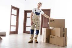 拆迁有纸板箱的服务人在公寓里屋子  搬家工人在家 在制服和许多箱子的工作者装载者在房子里 免版税库存照片