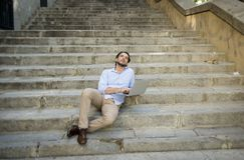 拉丁人坐城市楼梯与看起来的便携式计算机一起使用满意和确信 免版税库存图片