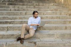 拉丁人坐城市楼梯与看起来的便携式计算机一起使用满意和确信 免版税图库摄影
