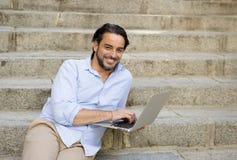 拉丁人坐城市楼梯与看起来的便携式计算机一起使用满意和确信 免版税库存照片