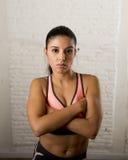拉丁体育妇女摆在剧烈的和badass面对与适合亭亭玉立的身体的表示 库存照片