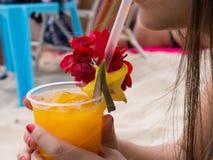 拉丁在海滩的妇女饮用的芒果汁 图库摄影