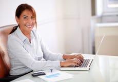 拉丁女实业家与她的膝上型计算机一起使用 免版税库存图片