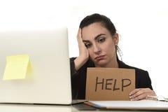 拉丁妇女陈列帮助标志绝望痛苦重音在工作,当坐在办公室膝上型计算机时 免版税库存图片