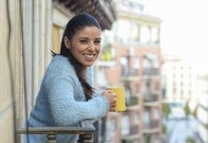 拉丁妇女饮用的咖啡或茶微笑愉快在公寓窗口阳台 免版税库存照片