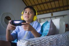 拉丁小孩在网上激动的和愉快的使用的电子游戏与拿着控制器的耳机享用获得乐趣坐cou 免版税库存照片