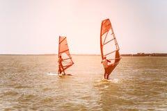 拉丁文在一起航行在一个风帆冲浪的委员会的海夫妇男人和妇女,当在度假在南部时的 库存照片