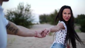拉丁文的概念,年轻夫妇,握在沙子跑的手赤足,握她的恋人的手的妇女,向前跑 影视素材
