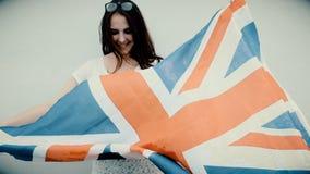 年轻拉丁美州的妇女拿着在她的身体前面的英国国旗旗子充满自豪感和喜悦,看起来粒状老英尺长度的葡萄酒 股票录像