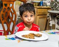 拉丁美州的孩子在与滑稽的表示的桌上坐他的面孔 库存图片