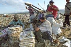 拉丁美州的男孩收集在垃圾填埋,尼加拉瓜的老纸 图库摄影