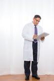 拉丁美州的男性佩带的实验室外套和举行剪贴板 免版税库存照片